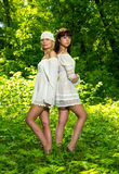 Two girls in a green forest Royalty Free Stock Photo