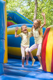 Two girls grimacing happily jumping on inflatable trampoline Royalty Free Stock Image