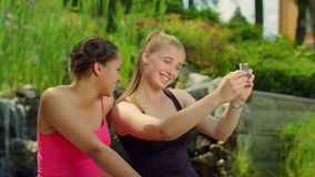 Two girls grimacing when taking photo with phone. Self portrait. Young women posing when taking photo in park. Female friends take photo with smart phone stock footage