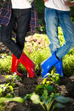 Two girls in gumboots posing on garden bed at hot summer day Stock Images