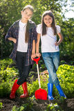 Two girls in gumboots posing with shovel on garden bed Royalty Free Stock Images