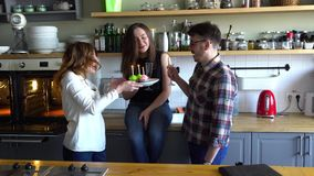 Two girls and guy blow out candles on the cupcake at the kitchen on muffine. Two young women and young men blow out candles on muffine at the kitchen with stock video