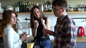 Two girls and guy celebrate birthday and clink glasses with champagne and eat cupcakes on the kitchen. Two young women and young men have a party, toast on the stock video