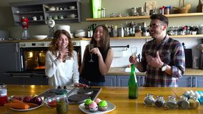 Two girls and guy celebrate birthday and clink glasses with champagne on the kitchen stock footage
