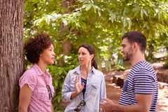 Two girls and a guy chatting Royalty Free Stock Photography