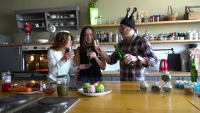 Two girls and guy in crazy hat celebrate birthday and clink glasses with champagne on the kitchen. Two young women and young man in crazy hat have a party, toast stock footage