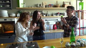 Two girls and guy eat muffins and laughing together. Two young women and young men have a party, eat cupcake on the kitchen and drink champagne smiling and stock footage