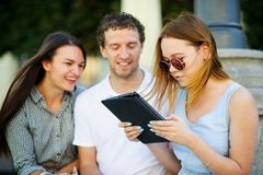 Two girls and the guy with interest look at the tablet screen. Friends cheerfully communicate Royalty Free Stock Images