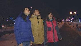 Two girls and a guy looking up. Two girls and a guy looking up at the night sky stock footage