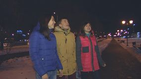 Two girls and a guy looking up. Two girls and a guy looking up at the night sky. Marvel and rejoice stock footage