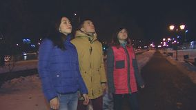 Two girls and a guy looking up. Two girls and a guy looking up at the night sky. Are silent stock video footage