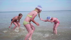 Two girls and a guy splashing water on the beach. Twins pour water on a hot summer day, laughter and good mood of. Twins pour water on a hot summer day, laughter stock video