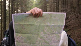 Two girls and a guy use a map and looking in the camera in the forest stock video