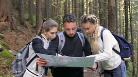 Two girls and a guy using a map to find a way in the forest stock video footage