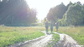 Two girls and a guy walking along a country road against a forest in summer in good weather at sunset. 1 stock footage