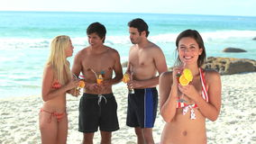 Two girls and guys standing together on the beach. With cocktails stock footage