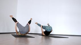 Two girls in the gym perform an exercise klubochalka. Pilate hassel. Lezhnaya on her back with her legs raised make a. Roll on her back stock footage