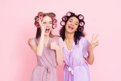 Two girls with hair curlers. They are celebrating women`s day March 8. Stock Image