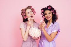 Two girls with hair curlers eating marshmellows. They are celebrating women`s day March 8. Royalty Free Stock Photography