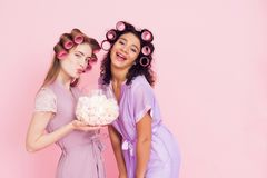 Two girls with hair curlers eating marshmellows. They are celebrating women`s day March 8. Royalty Free Stock Image