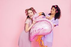 Two girls with hair curlers and flamingo baloon. They are celebrating women`s day March 8. Stock Photography