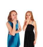 Two girls with hands over there mouth. Two pretty teen girls in blue and black dresses standing with there hands over there mouth, isolated for white background royalty free stock image