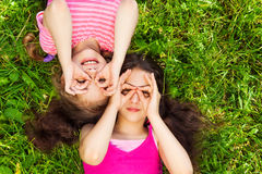 Two girls with hands round shape on face Stock Photos