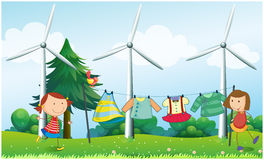 Two girls hanging their clothes near the windmills Royalty Free Stock Photo