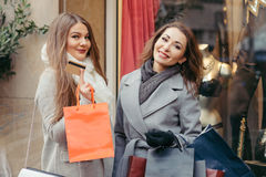 Two girls are happy with a credit card by the shopping. Two beautiful girls are happy with a credit card by the shopping Stock Photos