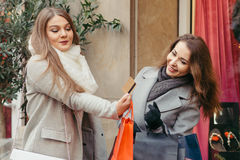 Two girls are happy with  a credit card by the shopping. Two beautiful girls are happy with a credit card  by the shopping Royalty Free Stock Images
