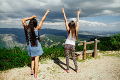 Two girls happy dance on peal of mountains Stock Photo