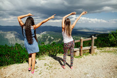 Two girls happy dance on peal of mountains Royalty Free Stock Images