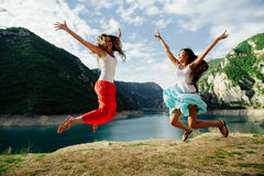 Two girls happy jump in mountains Stock Image
