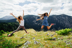 Two girls happy jump in mountains Royalty Free Stock Images