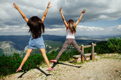 Two girls happy jump in mountains Royalty Free Stock Photos