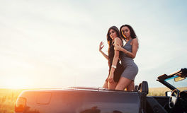 Two girls happy to pose next a black car. Against the sky on a fantastic sunset Royalty Free Stock Images