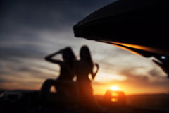 Two girls happy to pose next a black car. Two girls happy to pose next to a black car against the sky on a fantastic sunset. Natural blurred background. Soft Royalty Free Stock Photo