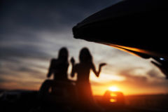 Two girls happy to pose next a black car. Two girls happy to pose next to a black car against the sky on a fantastic sunset. Natural blurred background. Soft Stock Photography