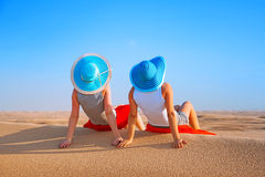 Two girls in hats relaxing in the desert. Safari of UAE stock images