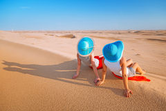 Two girls in hats relaxing in the desert Royalty Free Stock Images