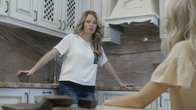 Two girls have conversation in the kitchen. At morning stock video