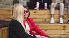 Two girls have conversation sitting at wooden elevation stock video