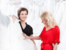 Two girls have a good look at the wedding dress. Preparing to try it on royalty free stock photos