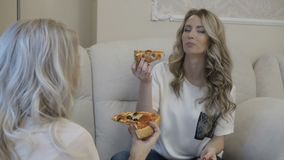 Two girls have pizza lunch. Two attractive blonde girls have pizza lunch stock footage