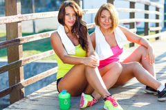 Two girls have a rest after exercising outdoors Stock Image