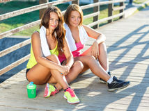 Two girls have a rest after exercising outdoors Royalty Free Stock Photography