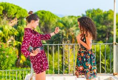 Two girls having an argument and accusing of misdoings. Two young female girls having a vivid conversation on the park. A vivid argument and discussion between stock photo
