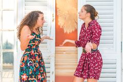 Two girls having an argument, what are you saying. Two young female girls having a vivid conversation on the park. A vivid argument and discussion between stock image