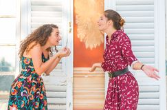 Two girls having an argument. Two young female girls having a vivid conversation on the park. A vivid argument and discussion between friends. Italian hand sign stock images