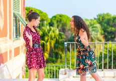 Two girls having an argument. Two young female girls having a vivid conversation on the park. A vivid argument and discussion between friends. Italian hand sign stock image